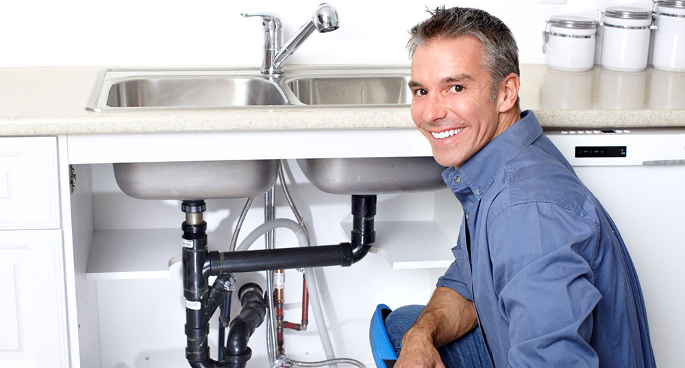Man smiling with faucet in background