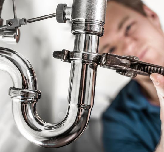 Man fixing a water faucet   Plumbing