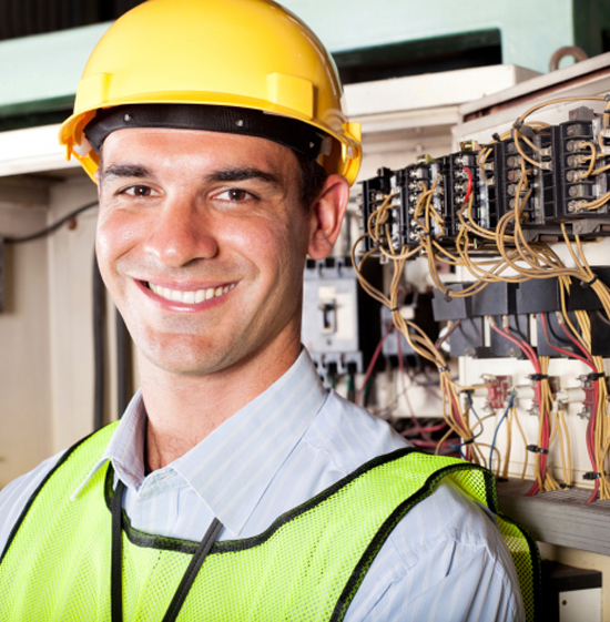 An image of a smiling electrician with electric switches in the background